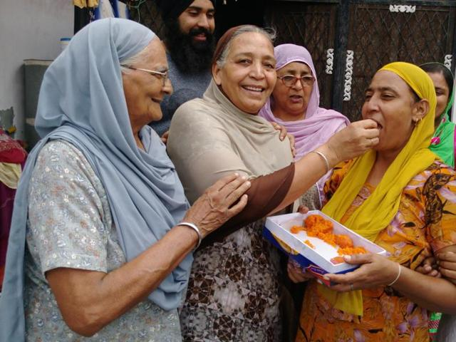 Relatives offer sweets to Gurdip Singh's wife Kulwinder Kaur.