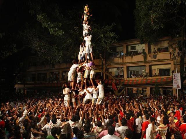 Devotees form a human pyramid to break a 'Dahi Handi' during Janmashthami celebration at Ghatkopar (E) in Mumbai.