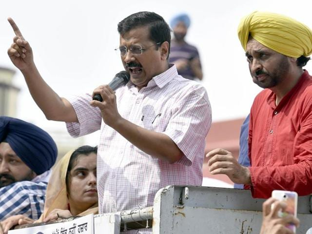 AAP chief and Delhi CM Arvind Kejriwal, flanked by party leaders Bhagwant Mann and Baljinder Kaur, addresses supporters outside Circuit House before appearing in court in Amritsar on Friday.