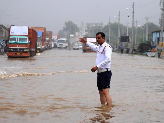 A traffic constable manages the traffic at Hero Honda Chowk on July 29, 2016,  after the  heavy rainfall a day earlier.  The chowk was submerged in up to  4 ft due to Badshahpur drain overflowing.