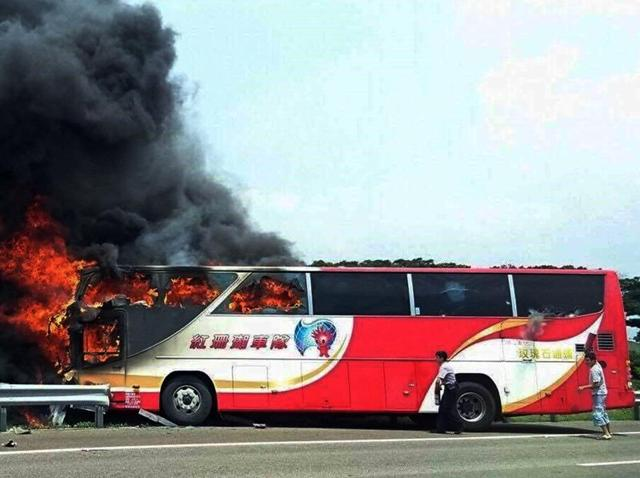 In this photo provided by Yan Cheng, a policeman and another man try to break the windows of a burning tour bus on the side of a highway in Taoyuan, Taiwan, on Tuesday, July 19, 2016.