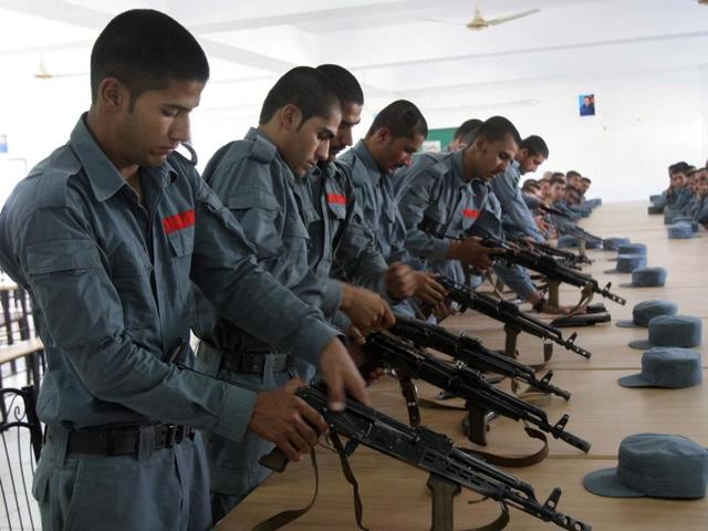 In this Sunday, July 24, 2016 photo, Afghan police soldiers practice, in Lashkargah, capital of southern Helmand province, Afghanistan.