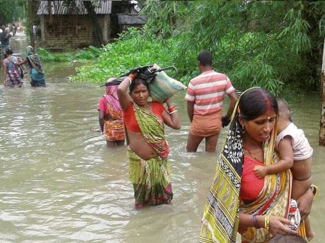 Villagers cross a flooded road in Katihar district of Bihar on Saturday.