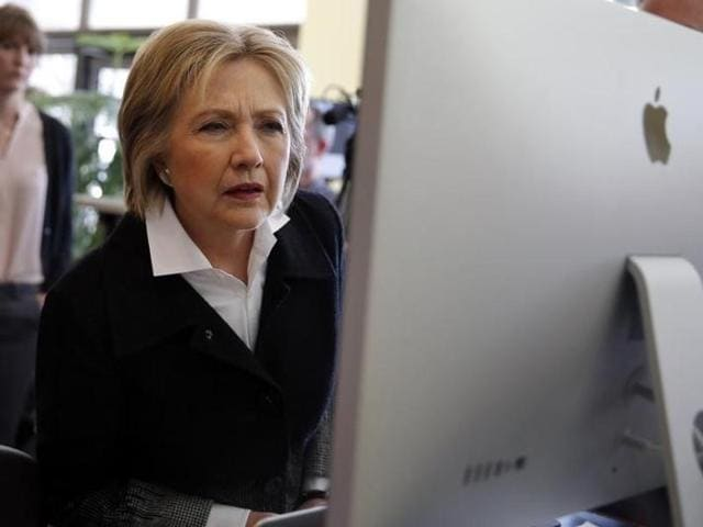 US Democratic presidential candidate Hillary Clinton looks at a computer screen during a campaign stop at Atomic Object company in Grand Rapids, Michigan.