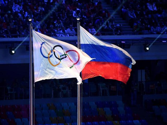 An Olympic Games flag and a Russian flag wave during the closing ceremony of the winter Olympics in Sochi.