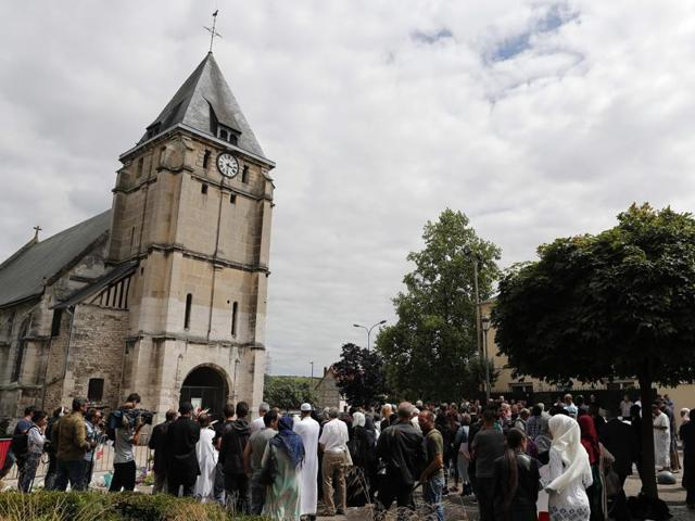Muslim worshippers gather in front of the memorial at the Saint Etienne church, in Saint-Etienne-du-Rouvray, Normandy.