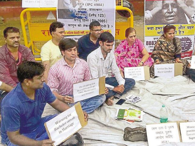 A group of men alleging harassment by their wives in false dowry cases sits on a dharna outside the collectorate on Saturday.
