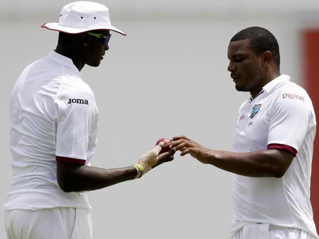 West Indies' captain Jason Holder, left, hand the ball to bowler Shannon Gabriel.