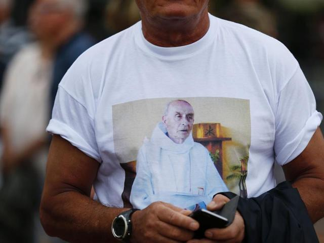A man wears a tee-shirt with the portrait of French priest Jacques Hamel, who was killed in a church during a hostage-taking claimed by Islamic State group.