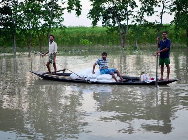 Villagers carry flood relief items on a country boat in flood-affected Pasahbari, near Guwahati, in Assam.