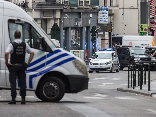 File photo of a police officer standing behind a van during a police intervention in central Brussels on July 20, 2016, to surround a