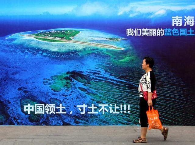 A woman walks past a billboard featuring an image of an island in South China Sea on display with Chinese words that read: