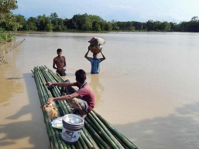 People shift to safe places from a flooded locality in Dharmanagar, North Tripura in this May 11 file photo. Months of heavy rains have battered the northeastern state badly.