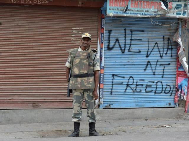 A paramilitary trooper stands guard during a curfew continued across large parts of Kashmir for the 23rd consecutive day in Srinagar on July 31, 2016.
