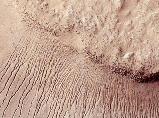"""Portions of the Martian surface shot by NASA's Mars Reconnaissance Orbiter show many channels from 1 meter to 10 meters wide on a scarp in the Hellas impact basin, in this photograph taken January 14, 2011 and released by NASA March 9, 2011.  These """"gullies"""" were believed to be evidence of water content on the Mars."""
