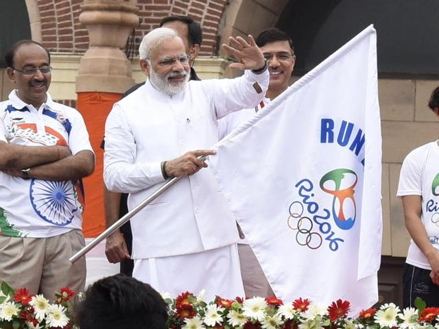 Prime Minister Narendra Modi with sports minister Vijay Goel waves at the public standing next to the statue of Major Dhyan Chand before flagging off 'Run for Rio'.