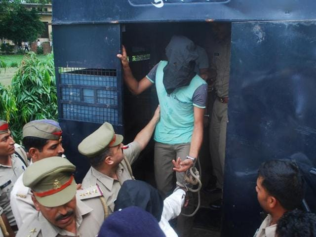 Police officials escort an accused in the Bulandshahr gangrape case to the court.