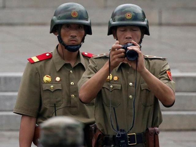 North Korean soldiers peep into a conference room during a ceremony marking the 63rd anniversary of the signing of the Korean War ceasefire armistice agreement at the truce village of Panmunjom, South Korea. Seoul prosecutors believe North Korea hacked into the email accounts of dozens of South Korean government officials this year.