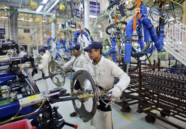 Employees work at the assembly line of a car manufacturing plant in Rajasthan.