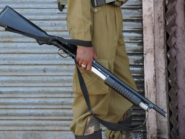 A paramilitary trooper holds a pellet gun during clashes with Kashmiri protestors in Srinagar.(AFP)