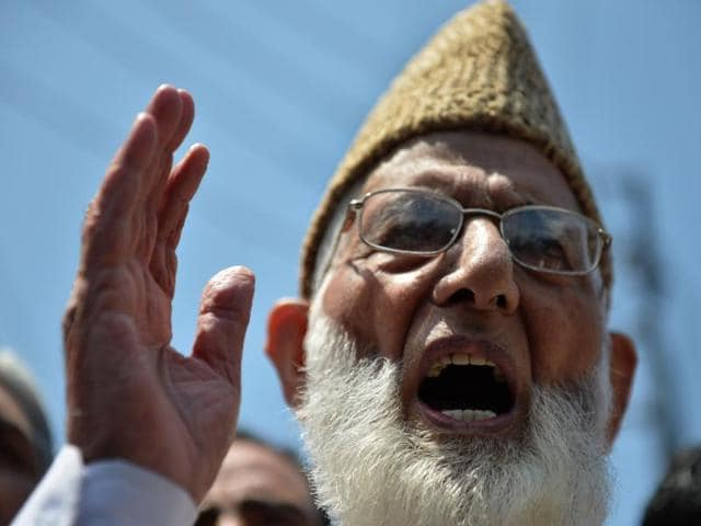 Senior separatist leader of the hardliner faction of All Parties Hurriyat Conference (APHC) Syed Ali Shah Geelani, center, with supporters outside his house in Srinagar.