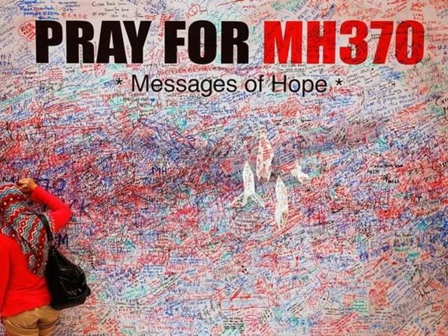 A woman leaves a message of support and hope for the passengers of the missing Malaysia Airlines MH370 in central Kuala Lumpur.