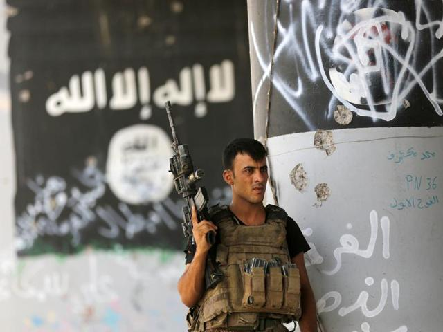 In this June 27, 2016 file photo, a member of a counterterrorism forces stands guard near Islamic State militant graffiti.