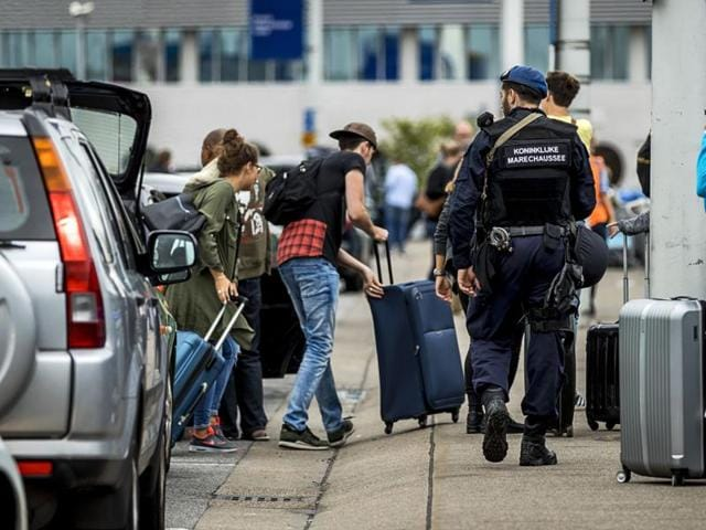 Netherlands' military police carry out additional patrols as passengers arrive to Schiphol Airport in Amsterdam. Security was stepped up in and around Amsterdam's Schiphol airport following a threat.