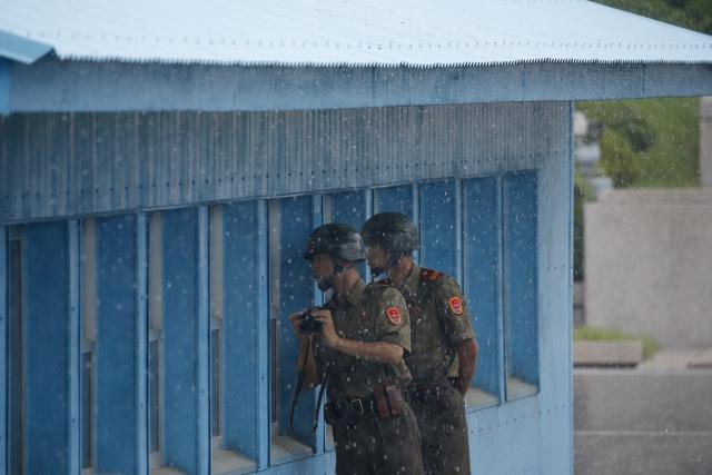 North Korean soldiers peep into a conference room in the United Nations Command Military Armistice Commission Conference Building during a ceremony marking the 63rd anniversary of the signing of the Korean War ceasefire armistice agreement at the truce village of Panmunjom, South Korea, Wednesday, July 27, 2016.