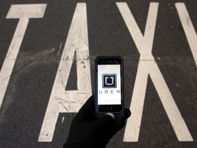 The logo of car-sharing service app Uber on a smartphone over a reserved lane for taxis in a street.