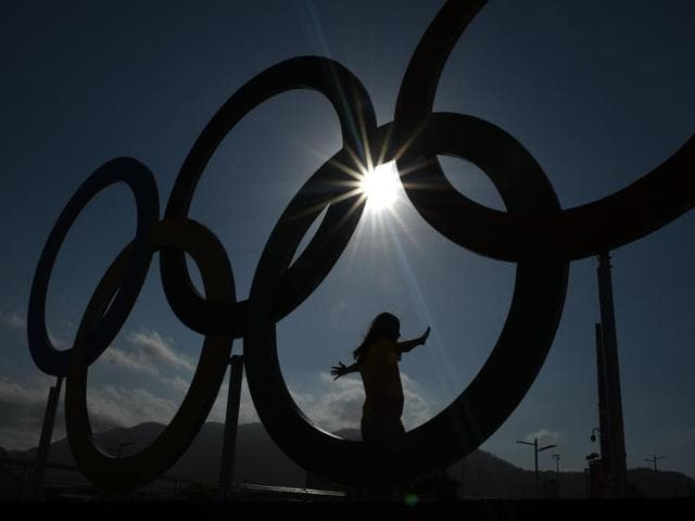 A woman is silhouetted as she poses with the Olympic rings at the Olympic park.