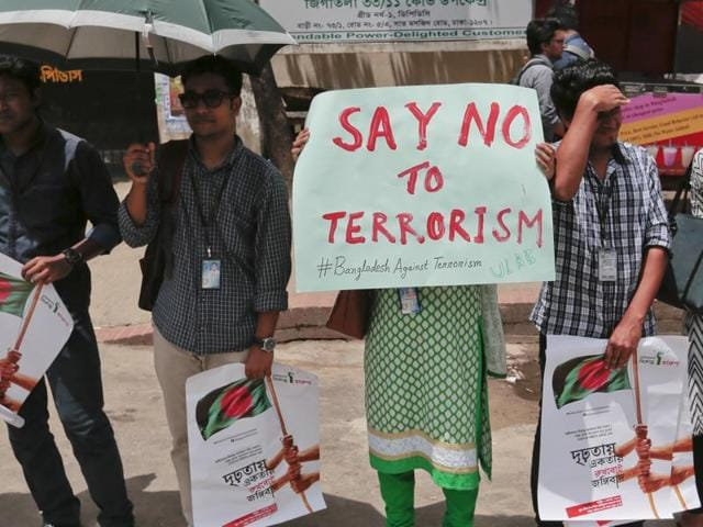 Bangladeshi students and teachers hold placards as they form a human chain to protest terrorism in Dhaka on Monday.