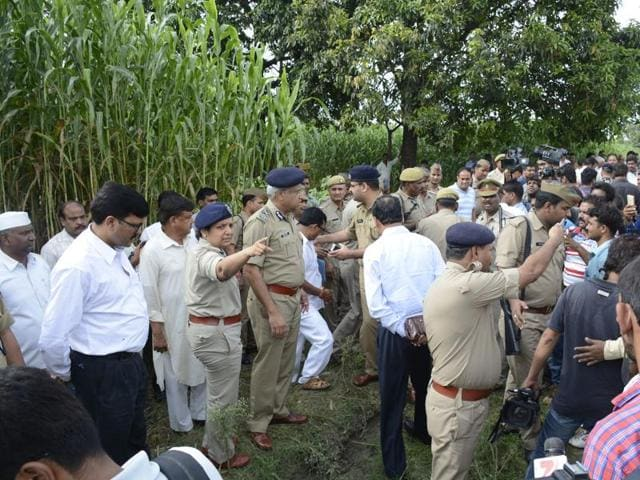 Senior police and administrative officials visit the area in fields of Dostpur village where a woman and her teenaged daughter were gangraped by armed robbers.