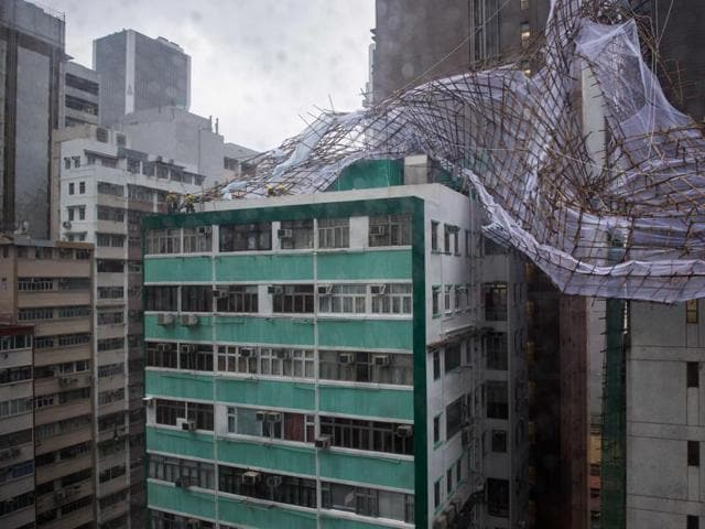 Rescue workers attempt to secure bamboo scaffolding that was damaged overnight at the top of a building in Hong Kong during a 'T8' storm signal raised for Typhoon Nida.