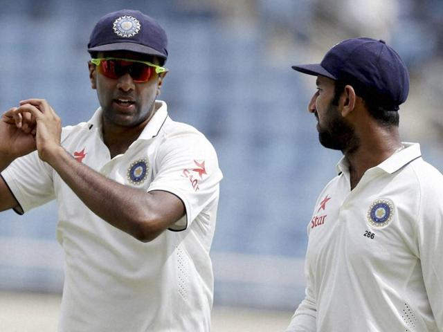 India's bowler Ravichandran Ashwin, left, talks to Cheteshwar Pujara.