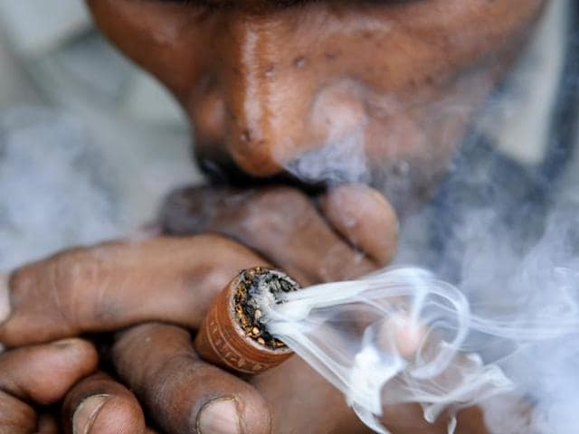 Shiva's portrait, chants mantras — oblivious to their long journey lying ahead on foot. Next to them, another group is busy puffing a chillum stuffed with marijuana — chanting Jai Bhole, after every puff.