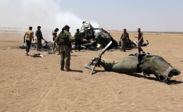 Syrian rebels gather around the wreckage of a Russian Mi-8 military transport helicopter after it was shot down along the administrative border between Idlib province, northwestern Syria.