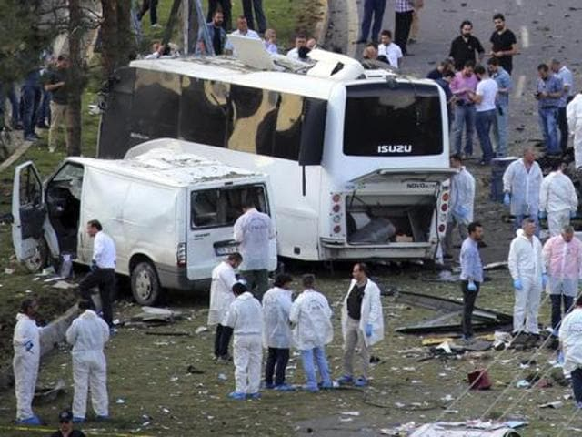 Security and forensic officers work at the explosion site after a car bomb struck a bus in Diyarbakir, Turkey.
