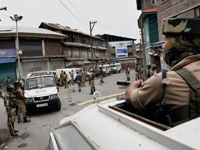 Securitymen patrol a street during curfew in Srinagar on Tuesday.