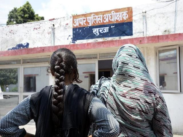 Women wait outside the office of the senior superintendent of police in Bulandshahr, where a woman and her teenaged daughter were robbed and raped on a highway, to report a crime.
