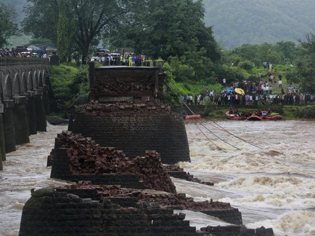 Rescue workers search the flooded Savitri River after an old bridge collapsed in Mahad, western Maharashtra.