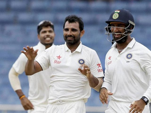 India's bowler Mohammed Shami, left, celebrates with teammate Cheteshwar Pujara, right, taking the wicket of West Indies' Darren Bravo.