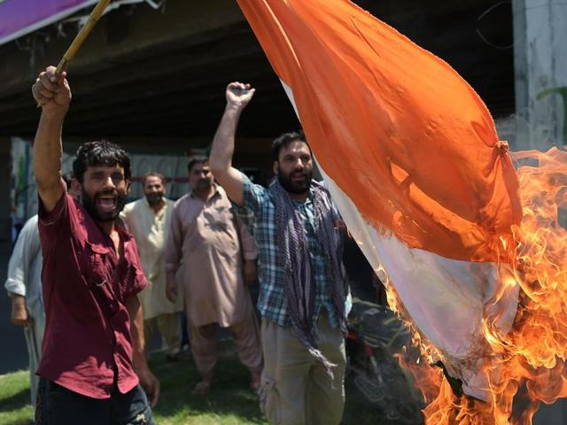 Pakistani Kashmiri protesters torch an Indian flag as they block a main highway ahead of the arrival of Indian home minister Rajnath Singh in Islamabad on Wednesday to protest his visit to Pakistan to attend the SAARC Home Ministers' conference.
