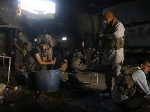 Syrian civil defence workers help an injured woman after warplanes attacked a street, in Aleppo, Syria. Intelligence agencies have identified 132 of some 650  Pakistanis fighting in conflict zones in Syria, Iraq, Yemen, Afghanistan and Central Asian states.