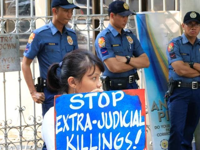 Anti-riot policemen stand guard in front of a protester holding a placard condemning the rise in extrajudicial killings in connection to the war on illegal drugs during a protest outside the Department of Justice in metro Manila, Philippines.