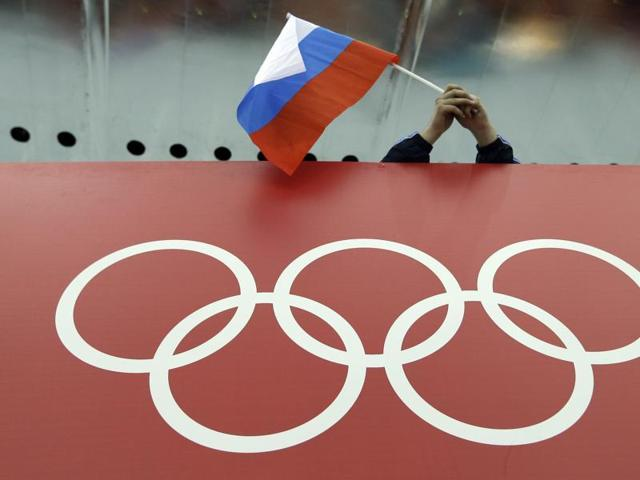 A file photo of Russian skating fan holds the country's national flag over the Olympic rings.