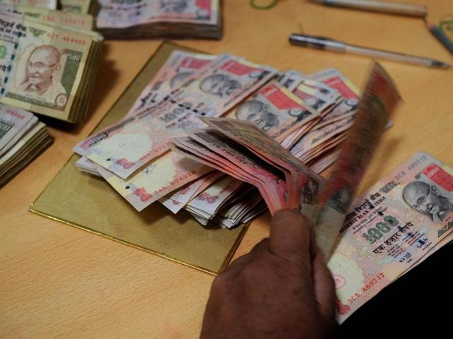 An employee counts currency notes at a bank in Mumbai.