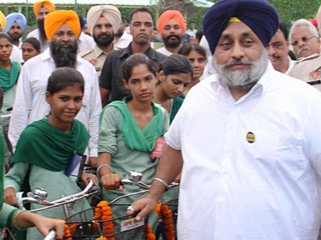 Deputy CM Sukhbir Singh Badal posing with students after distributing bicycles at Raikot near Ludhiana on Thursday.