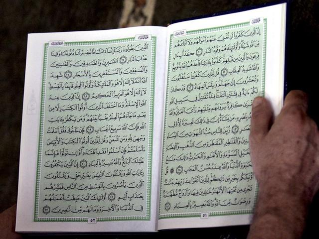 A Palestinian man reads from the Quran during 'fajr', or early morning prayers, in the first Friday of the Muslim holy fasting month of Ramzan.