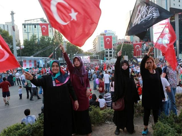 Women wave flags of Turkey as another holds a black flag with Islamic Arabic writing at the Kizilay Square during a protest against the failed military coup.